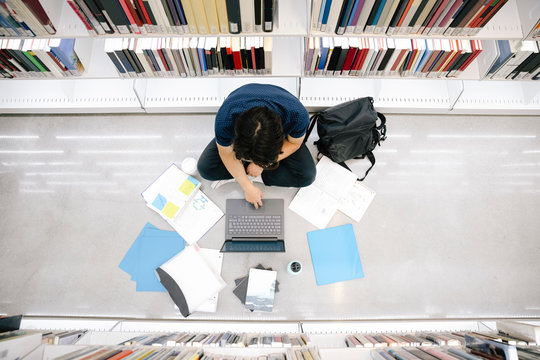 Overhead view of student using laptop in library
