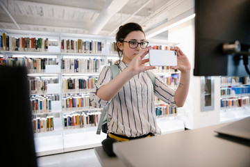 Student taking photo of library computer with smart phone