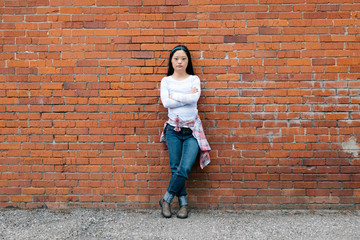 Portrait confident young woman with down syndrome leaning against brick wall