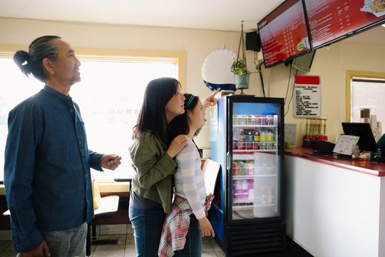 Family looking up at menu in drive-in