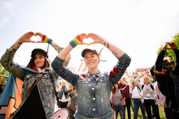 Students making heart shapes with hands at gay pride parade