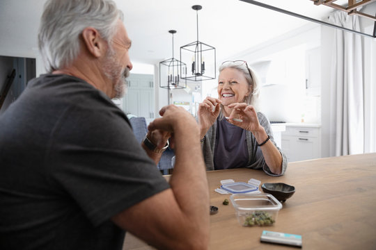 Happy senior couple rolling marijuana joints at dining table