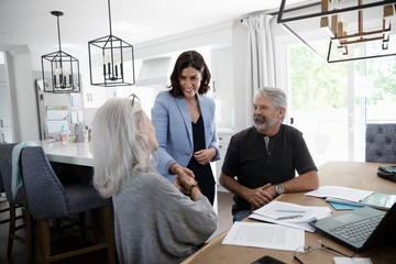 Financial advisor shaking hands with senior couple at dining table