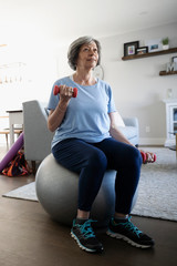 Senior woman exercising with dumbbells on fitness ball in living room