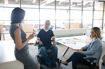 Businessman in wheelchair with female colleagues in office meeting