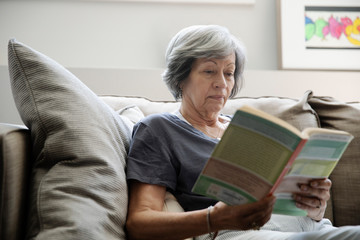 Senior woman reading book on living room sofa