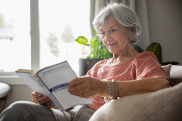 Senior woman reading book in living room