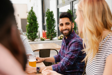 Smiling young man drinking beer with friends on brewery patio