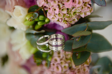 Close up of two golden wedding rings and bridal bouquet on mirror table, copy space. Selective...