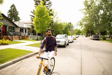 Young man riding bicycle on neighborhood street Fototapete