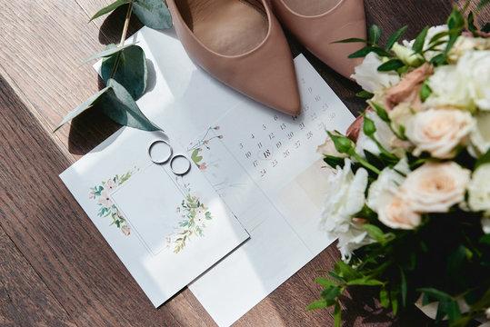 Luxury set of wedding invitations, wedding rings, elegant bride shoes on high heels on wood brown background. Honeymoon and wedding concept