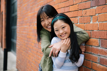 Portrait happy mother and daughter with down syndrome hugging at brick wall