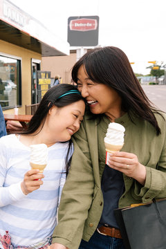 Happy mother and daughter eating ice cream outside drive-in