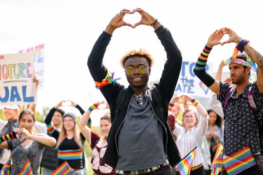 Student making heart shape with hands at gay pride festival