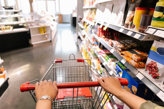 Personal perspective woman pushing shopping cart in grocery store