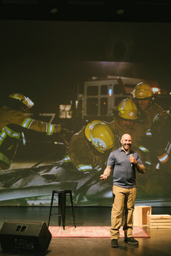 Male firefighter giving inspirational speech on stage
