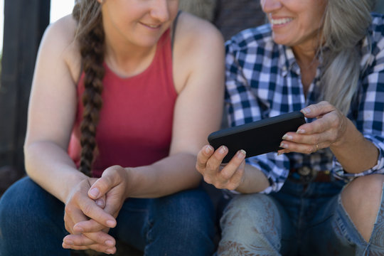 Cropped shot of mother and daughter looking at mobile phone