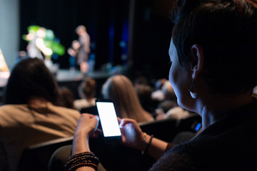 Woman using smart phone in audience