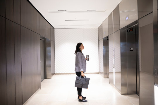 Businesswoman with coffee and briefcase waiting for elevator