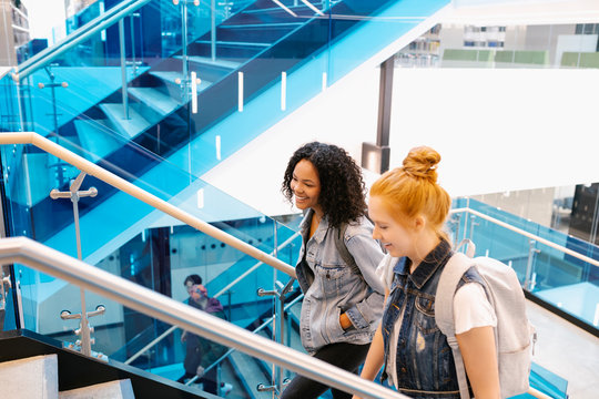 Two female students walking up staircase in modern university