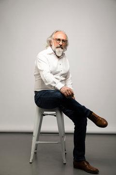 Portrait confident senior businessman with eyeglasses and gray beard