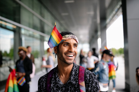 Portrait of student on gay pride rally with rainbow flag in bandanna