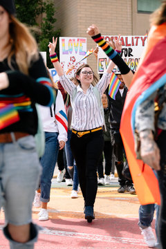 Student marching with arm raised at gay pride festival