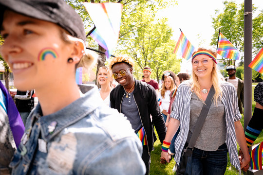Cheerful students with rainbow flags at gay pride festival