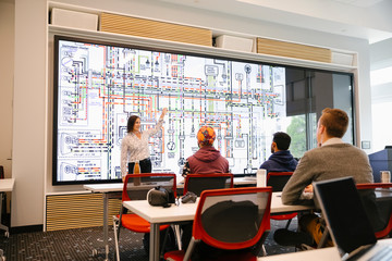 Engineering students listening to teacher explain diagram on whiteboard