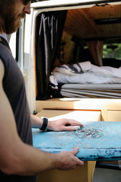 Male surfer waxing surfboard at back of camper van