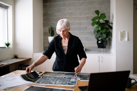 Creative female senior designer reviewing proofs in office