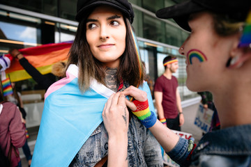 Couple on gay pride march wearing rainbow flag