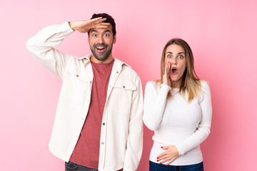 Couple in Valentine Day over isolated pink background surprised and shocked while looking right