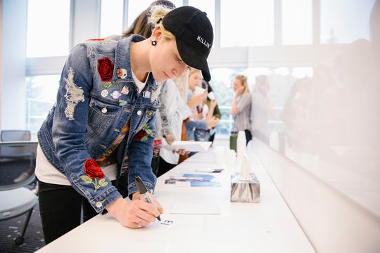 Student wearing denim jacket and cap making notes in classroom