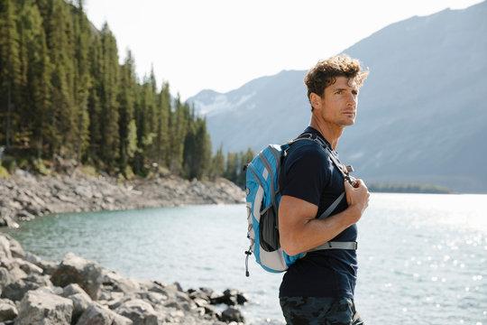 Portrait confident male hiker at sunny lakeside