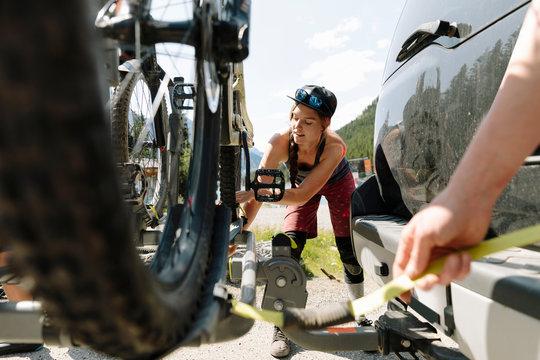 Woman unloading mountain bike from trailer