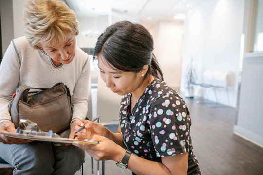 Female nurse helping senior woman fill out paperwork in clinic waiting room