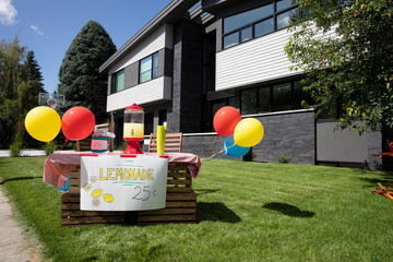 Balloons on lemonade stand in sunny, summer front yard of house