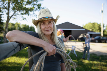Portrait of senior woman holding rope on ranch