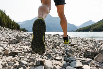 Man running over rocks along sunny lakeside