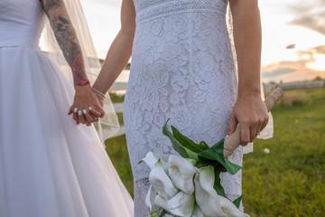 Affectionate lesbian brides with bouquet holding hands Fotobehang
