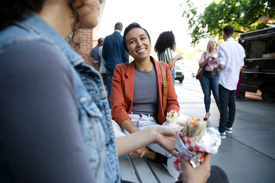 Smiling businesswoman eating burrito outside Food truck