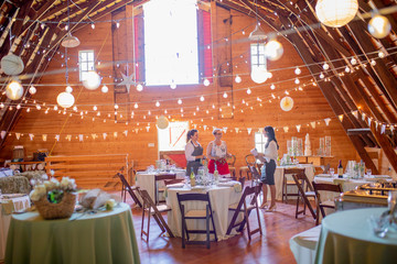 Wedding planner and workers preparing for wedding reception in barn