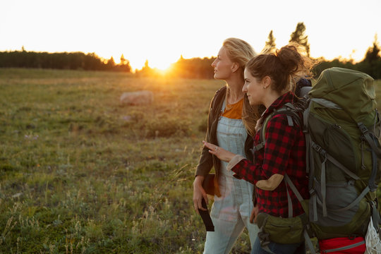 Two women hiking with camping gear