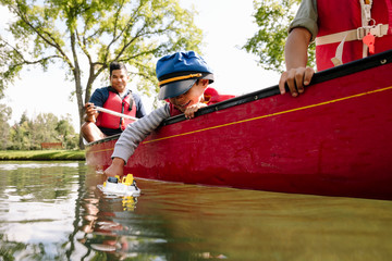 Young boy playing with toy boat in canoe
