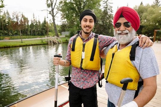 Portrait of mature Indian man and son wearing life jackets