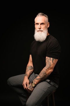 Portrait confident, handsome man with gray beard and tattooed arms
