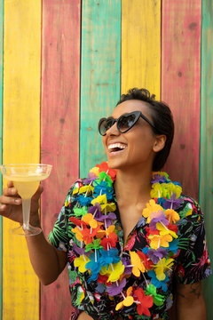 Portrait carefree, playful young woman wearing leis and drinking margarita on summer patio