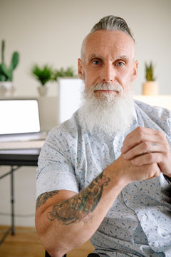 Portrait confident businessman with tattoos and white beard