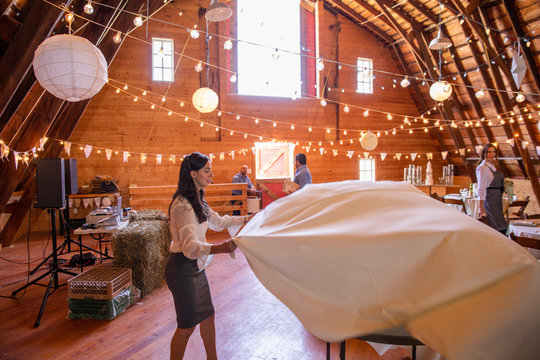 Female wedding planner placing tablecloth on wedding reception table in barn